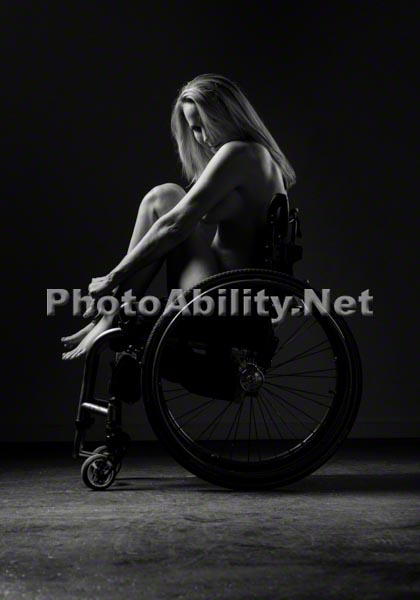 Nude woman in a wheelchair posing in a studio