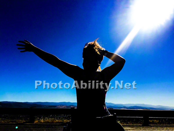 Young woman in a wheelchair silhouetted against the sun