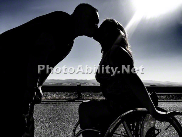 Young woman in a wheelchair kissing her boyfriend silhouetted against the sun