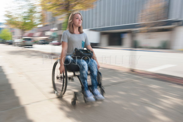 Young woman speeding in her wheelchair