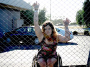Young-woman-in-wheelchair-against-chain-mail-security-fence