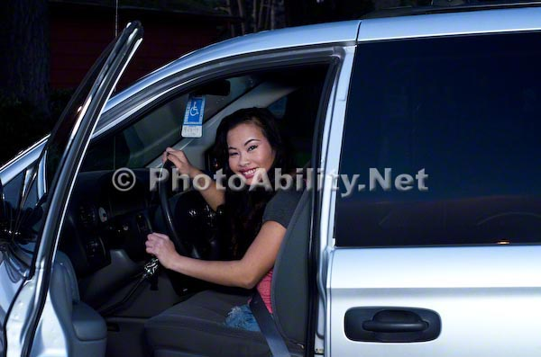 Young amputee woman in her car