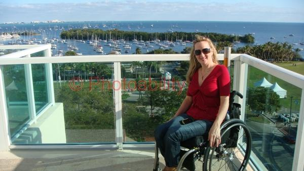 Woman in a wheelchair on a resort balcony overlooking a marina