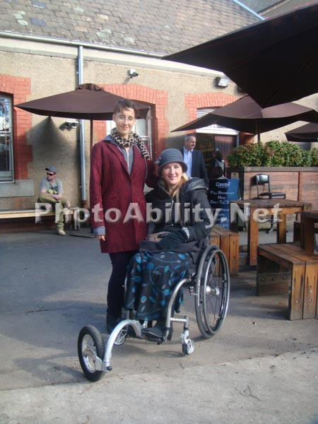 Mother in a wheelchair with her daughter at an outdoor restuarant