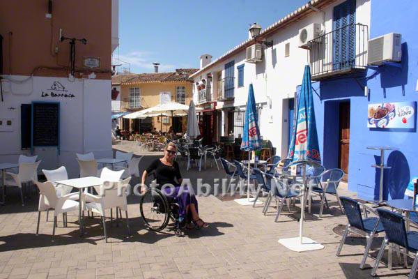 Woman tourist in a wheelchair exploring a mediterranean village square