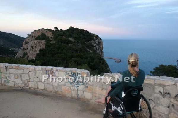 Woman tourist in a wheelchair at an ocean viewing lookout