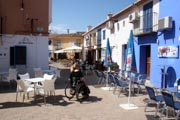 Woman-tourist-in-wheelchair-exploring-mediterranean-village-square