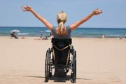 Woman-in-wheelchair-enjoying-sunny-afternoon-at-the-beach