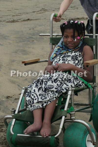 Young girl in a beach wheelchair