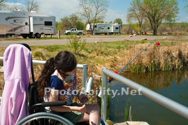 Young girl in a wheelchair fishing at an RV park