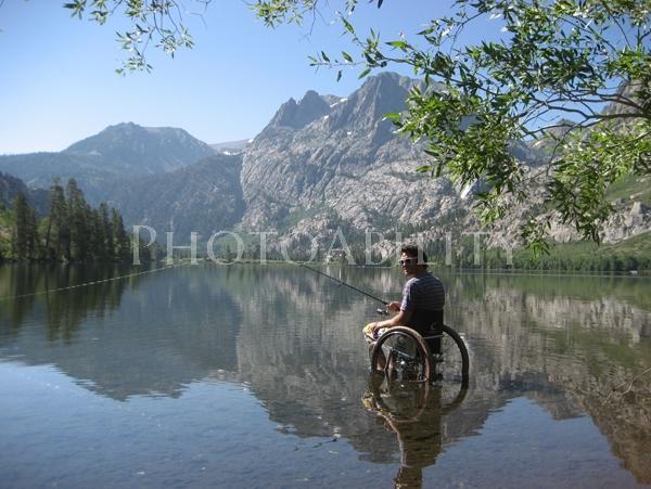 Man in a wheelchair fishing in a mountain lake