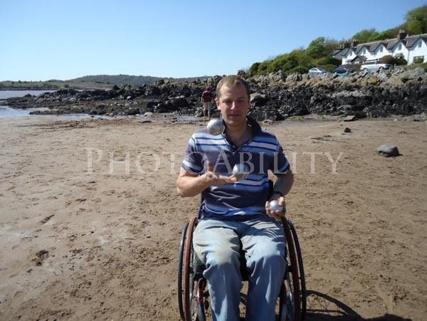 A young man using a wheelchair playing bocci on a beach