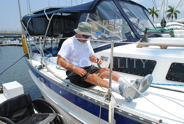 Sailor in a wheelchair with his yacht at the dockMature man in a wheelchair boarding his yacht