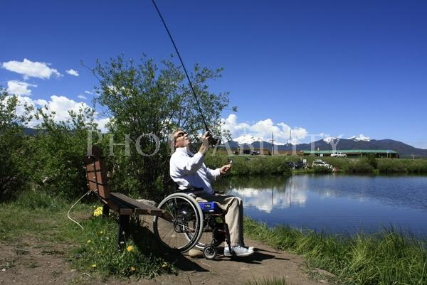 Man in a wheelchair casting his fishing rod into a lake