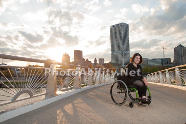 Young woman in a wheelchair exploring a coastal city park on sunset