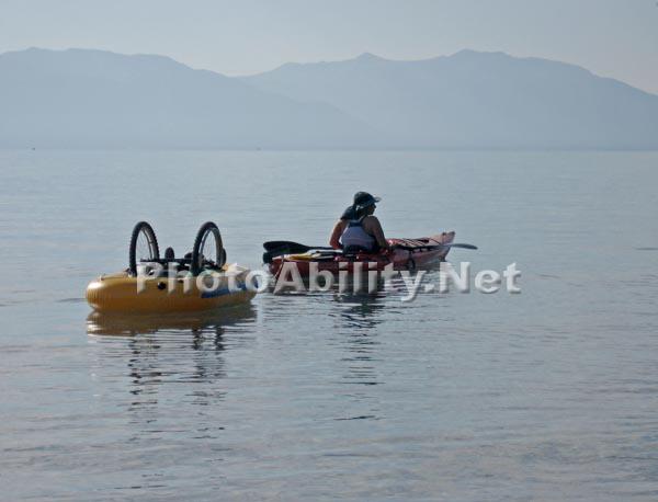 Woman kayaking on a mountain lake towing her wheelchair