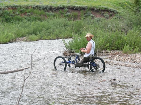 Man in an off road handcycle fishing in a mountain stream