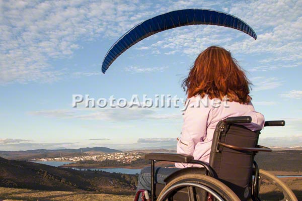 Young woman in a wheelchair on a hillside watching paragliders