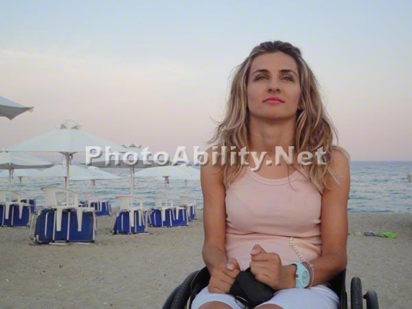 Young woman using a wheelchair on a beach at sundown