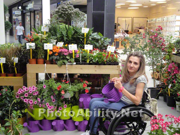 Young woman using a wheelchair at a flower stall in a mall