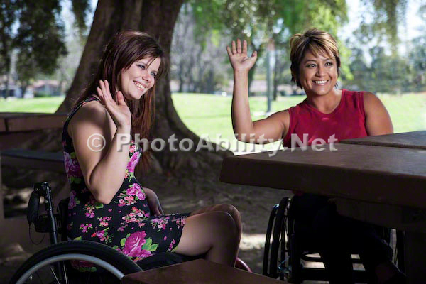 Two woman using wheelchairs at a park picnic table