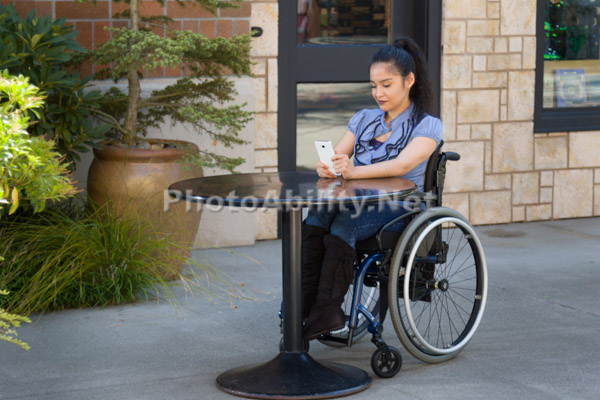 A young woman using a wheelchair conversing on a cell phone