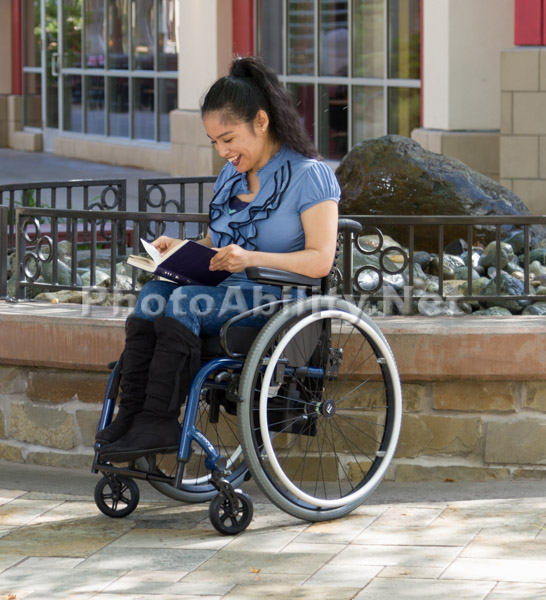 A young woman using a wheelchair reading a book by a fountain