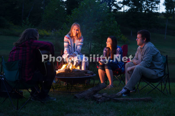 Young woman using a wheelchair sitting around a firepit with her friends