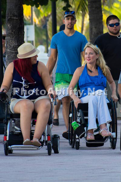 Two women in wheelchairs enjoying an afternoon in a seaside town
