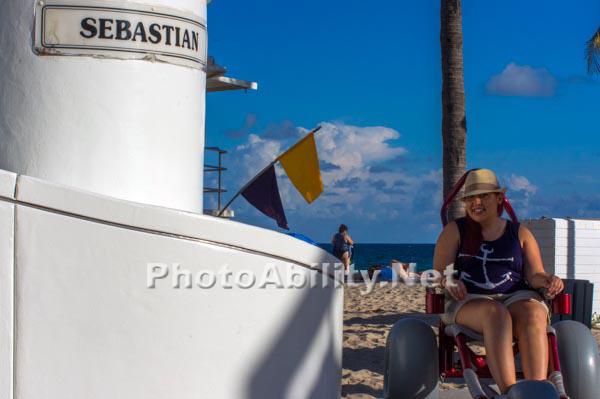 Young woman enjoying the ocean in a beach wheelchair