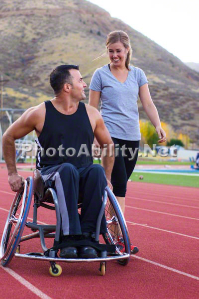 Athletic man in a wheelchair hanging out and exercising at an outdoor track and field facility with a group of active friends.