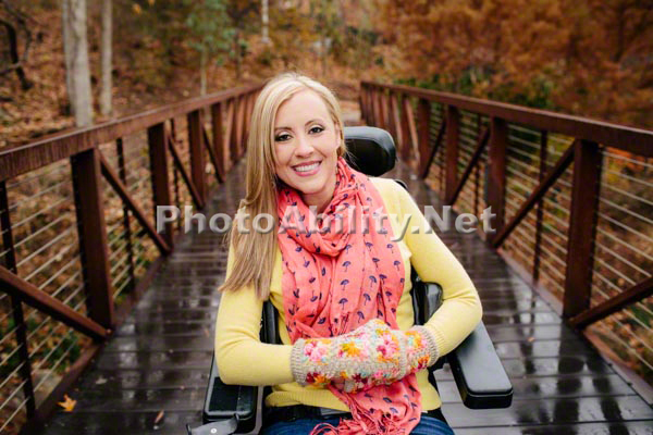 Woman in a power wheelchair in a riverside park during fall