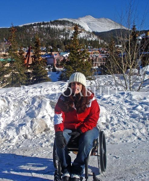 Young woman sitting in her wheelchair in the snow at Breckenridge