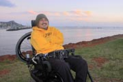 Man-in-power-wheelchair-in-coastal-park-overlooking-city-harbor-during-sunset