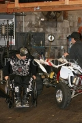 Young-man-in-wheelchair-working-on-his-quad-bike-in-workshop