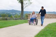 Young-woman-in-wheelchair-with-her-boyfriend-enjoying-the-views-overlooking-river-from-lookout.