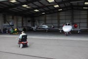 Man-with-disability;-who-is-wheelchair-user;-in-aircraft-hanger-preparing-to-fly-plane,