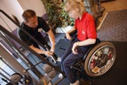 Access-to-services,-Fitness-instructor-and-disabled-woman-in-the-gym;-using-Jungle-Cable,