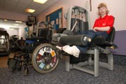 Access-to-services,-Disabled-woman-in-the-gym;-using-Leg-Extension,