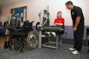 Access-to-services,-Fitness-instructor-with-disabled-woman-in-the-gym;-using-Leg-Extension,