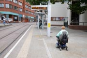 Woman-wheelchair-user-going-towards-tram-stop,