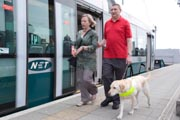 Vision-impaired-man-with-sighted-guide-and-guide-dog-walking-along-the-platform-at-the-tram-stop,