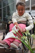 Wheelchair-user-with-Spina-Bifida-arranging-flowers-in-her-conservatory.
