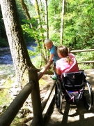 Woman-in-wheelchair-with-her-grandson-at-river-park