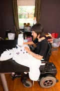 Young-female-fashion-designer-using-power-wheelchair-sewing-her-creation