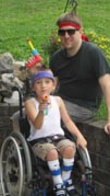 Young-boy-in-wheelchair-playing-with-water-pistols-with-his-father