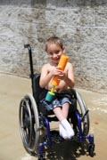 Young-boy-in-wheelchair-playing-with-supa-soaker-on-hot-summers-day