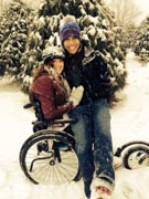 Young-woman-in-wheelchair-enjoying-snowfall-with-her-boyfriend.