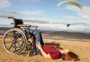 Yound-woman-in-wheelchair-on-hillside-watching-paragliders