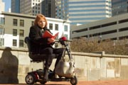 Woman-using-mobility-scooter-reading-book-in-city-park